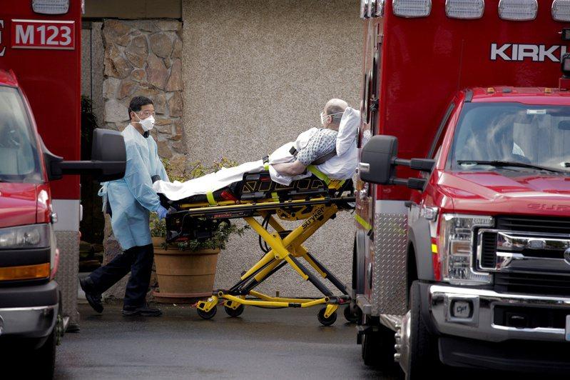 華盛頓州Kirkland郡是目前群聚感染重災區,救護人員將病患送上救護車。  路透