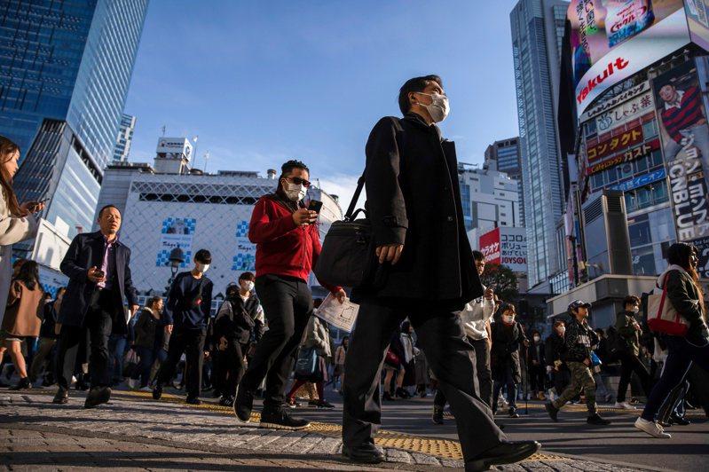行人戴著口罩走在東京澀谷購物區。  路透