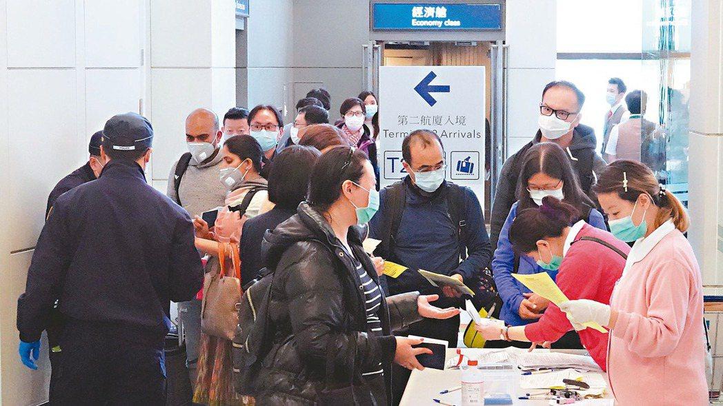 圖為支援的護士與保警在閘口一一要求入境旅客仔細填寫健康聲明卡。 報系資料照