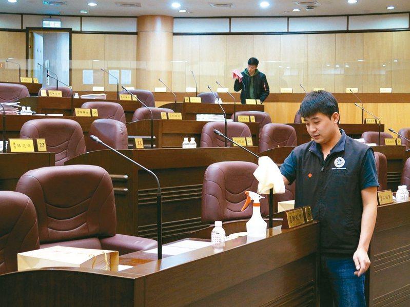 桃園市議會議程結束後,議會人員會以酒精逐一擦拭麥克風消毒。 記者張裕珍/攝影