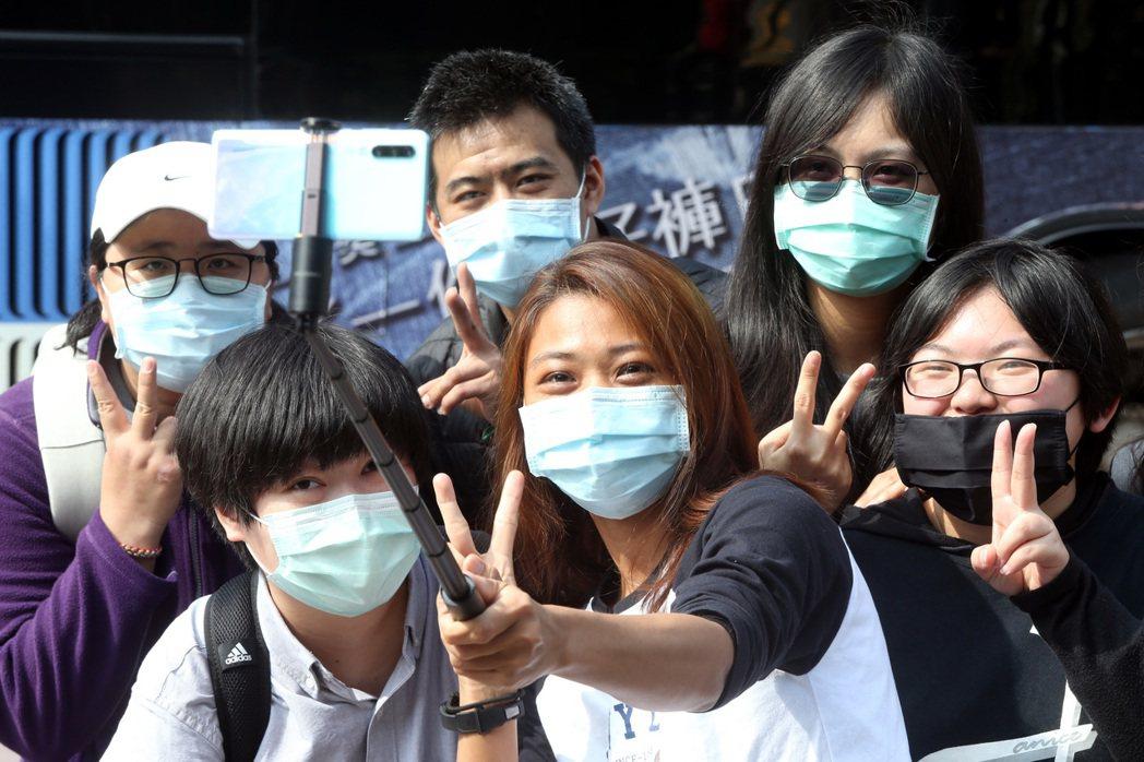 台灣防疫表現相當亮眼。圖為一群年輕人戴著口罩,在西門町拿起自拍棒合照。 圖/聯合...