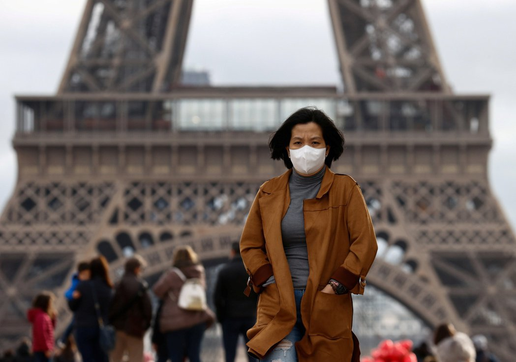 在歐洲,針對亞裔人士的種族歧視事件時有所聞。圖為一亞裔女子戴著口罩行經艾菲爾鐵塔...