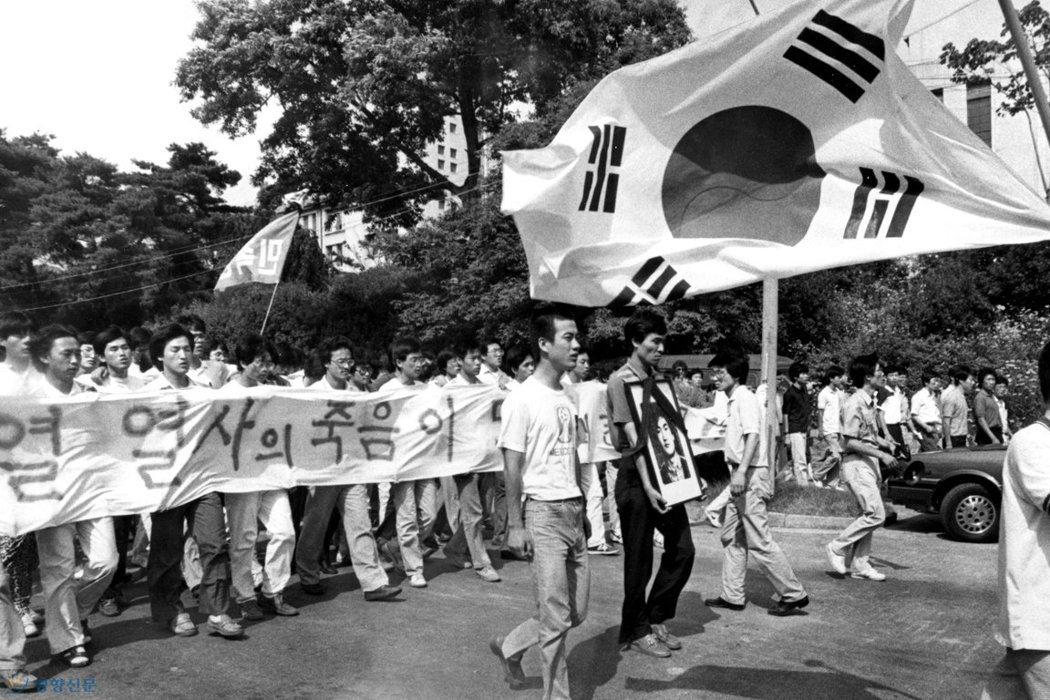 金英夏當年在延世大學的同學李韓烈,在「六月民主抗爭」中受傷身亡,這起事件激化了群眾的不滿。 圖/取自六月民主抗爭網站