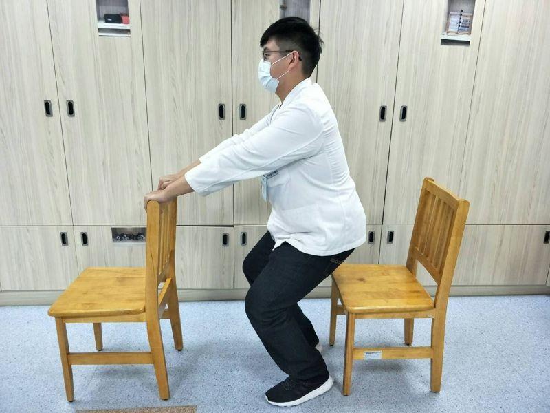 童綜合醫院物理治療師陳佑昇示範扶高背椅半蹲,腰挺直半蹲,再站立,蹲下去、站起來算一下,早晚各50下。圖/陳佑昇提供