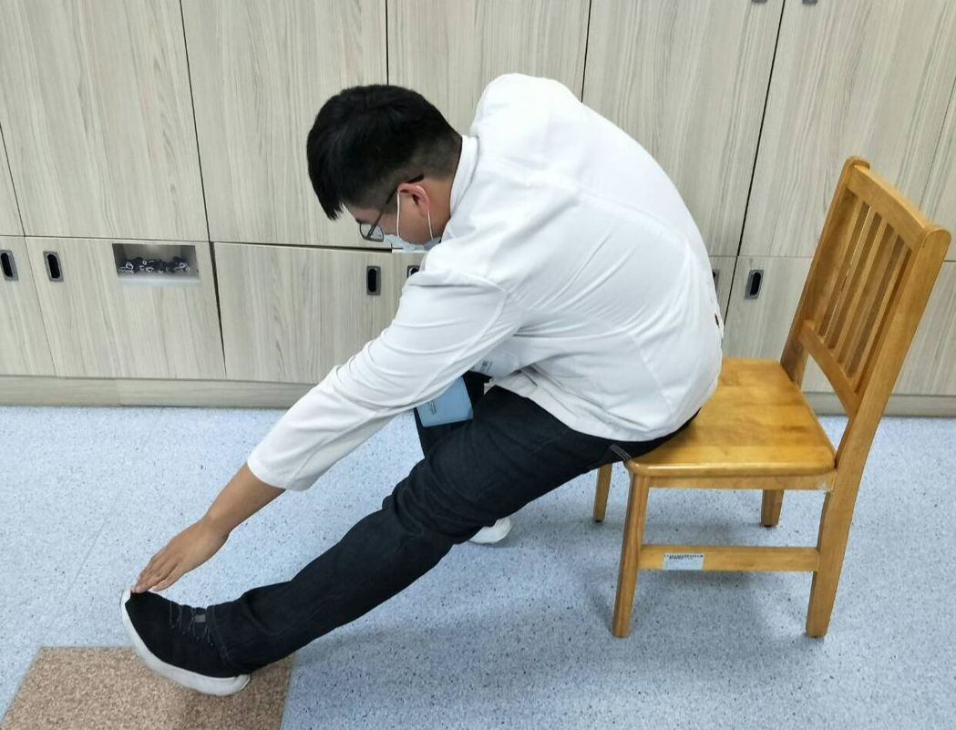 童綜合醫院物理治療師陳佑昇示範一腳伸直踩地,翹起腳尖,再以手摸腳尖,再換腳做,各...