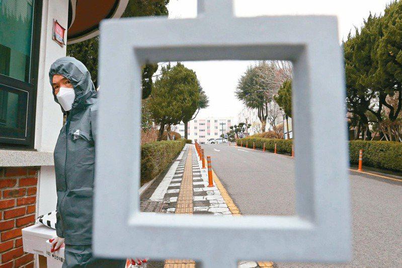 一名南韓衛生官員七日穿著防護裝,走進大邱被封鎖的社會住宅內。 (法新社)
