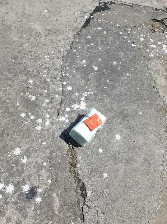 一名網友PO文分享,日前自己走在馬路上看到一大疊藍綠色的不明物體,上頭還綁了個紅包袋,沒想到湊近一看竟發現,原來紅包底下是一大捆「口罩」,但原PO卻發毛直呼「是不是該注意什麼」。圖擷自爆廢公社