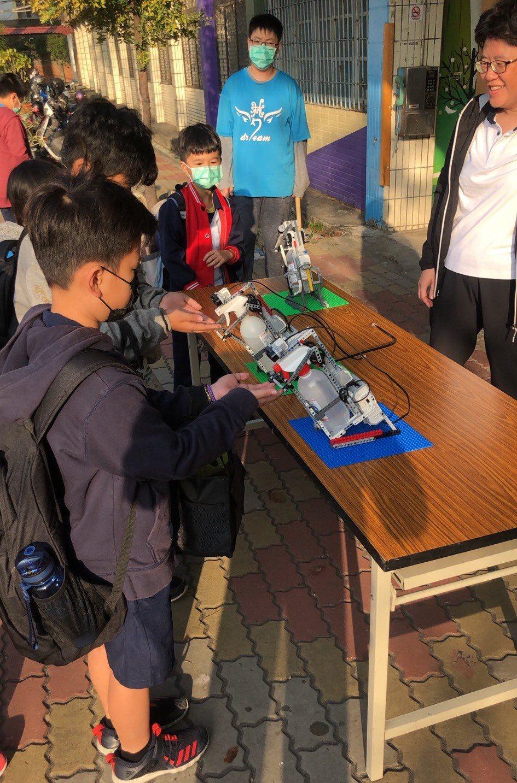 高雄市林園國小師生組裝「自動感應酒精消毒機器人」,小朋友們也愛用機器人幫忙消毒雙...