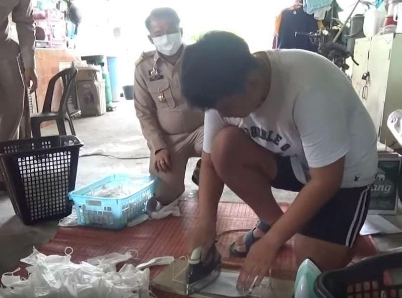 工人會以熨斗熨平口罩,掩飾鐵線曾屈曲的痕迹。圖/泰國民族報影片截圖