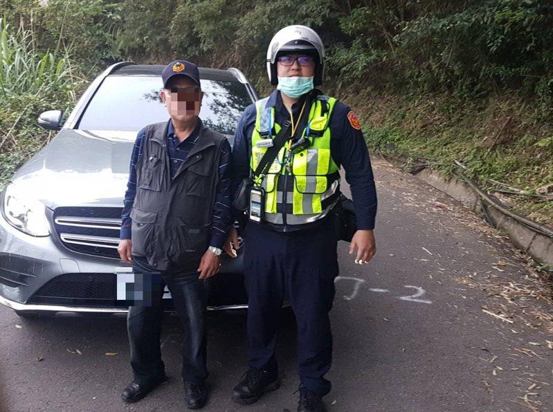 警員胡旭騰和路人合力幫忙抬車,終於讓賓士車脫困。記者鄭國樑/翻攝