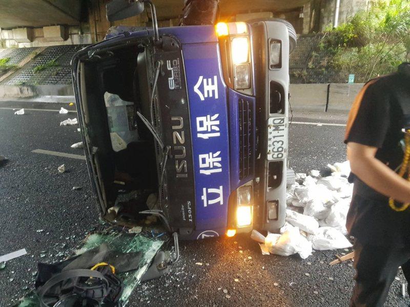 一輛保全公司運鈔車,行經國道3號接台北市環東大道翻覆,消防隊將兩名男保全送醫。記者李奕昕/翻攝