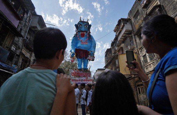 印度慶典「灑紅節」搬出一具巨大怪物像,身上還寫著「COVID-19」的字樣。 路透