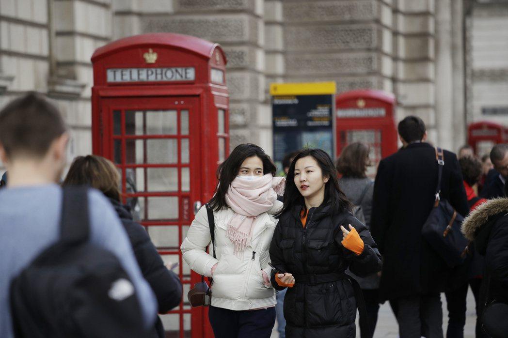 倫敦街頭的東方人,即便戴上口罩,卻還是圍上圍巾掩飾。 (美聯社)