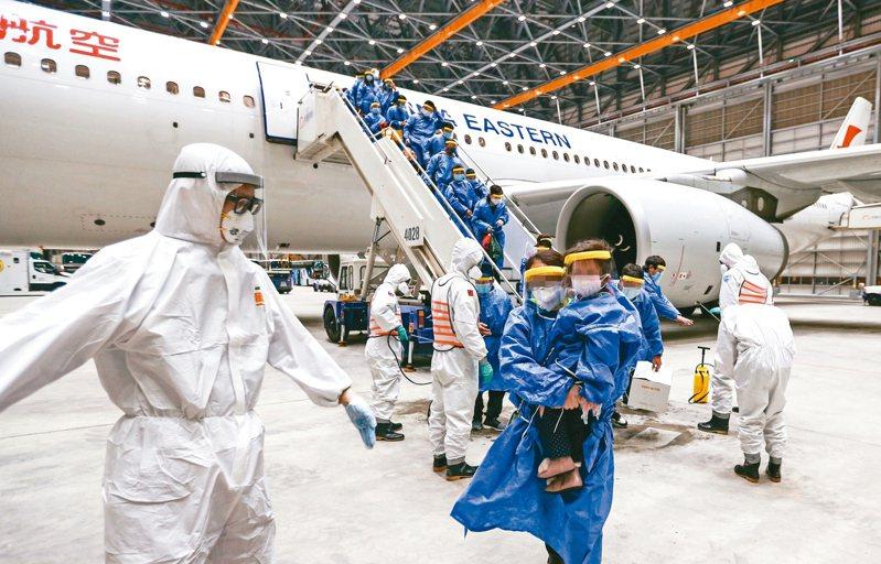 滯留大陸湖北多日的台商及眷屬昨天凌晨搭乘東方航空專機返國,在機場待命的化學兵立即檢疫和消毒。 圖/軍聞社