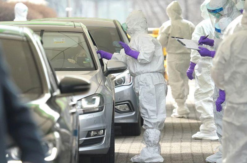 南韓得來速篩檢法,在車上由篩檢人員採檢體,每天可檢測上萬人。 路透