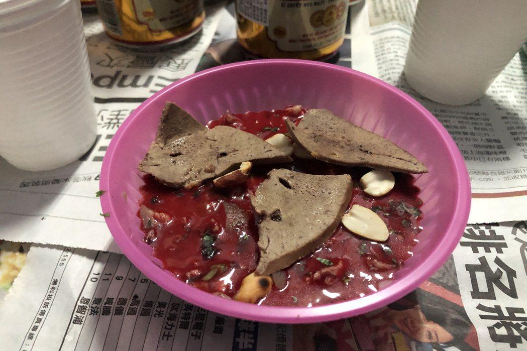 把薑、蒜、花生和新鮮豬血混在一起,凝固後先將豬肝、豬雜放在上面,要食用前會再滴幾...