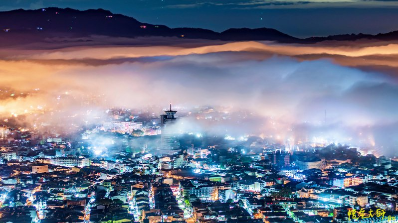 從埔里虎頭山往下拍攝,熱鬧的街景燈光在雲海中閃現,美不勝收。圖/莊家和提供