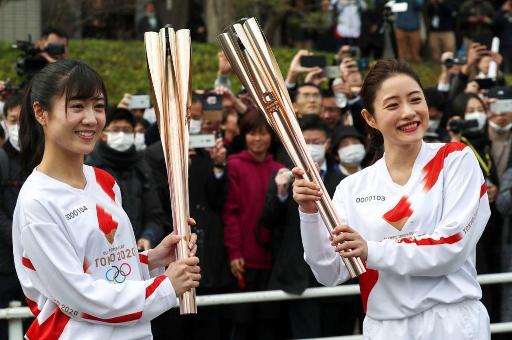 2月15日,日本女星石原里美(右)以火炬手身分為傳遞聖火採排,後方民眾因應疫情紛紛戴上口罩。 圖/路透社