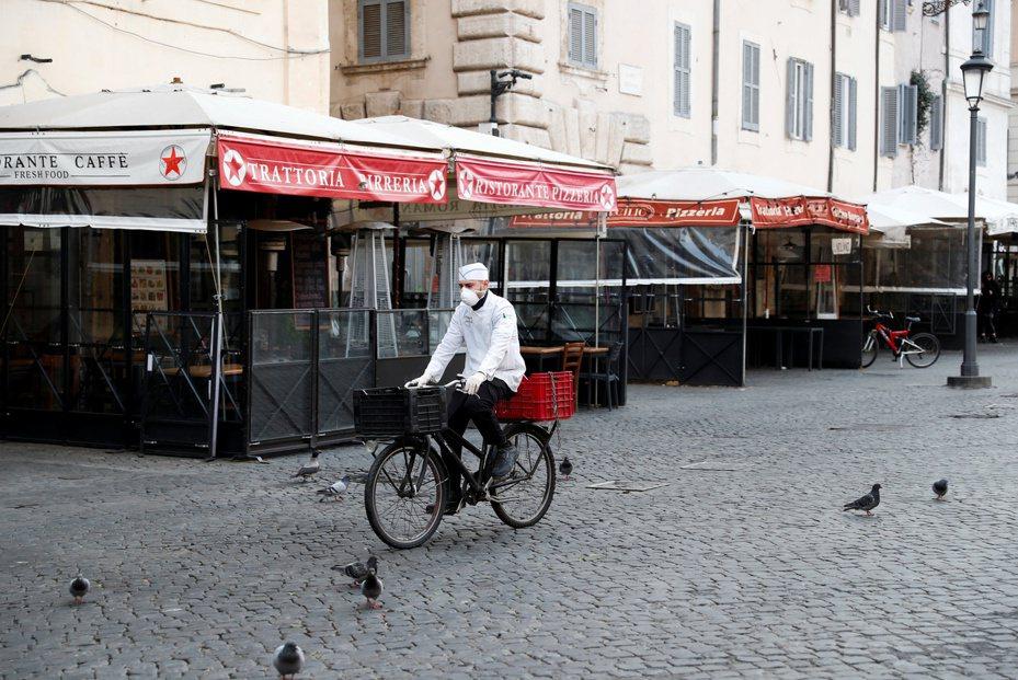 義大利因疫情嚴重,10日起全國封鎖,圖為11日的羅馬市鮮花廣場,一名外送員戴著口罩騎自行車。路透