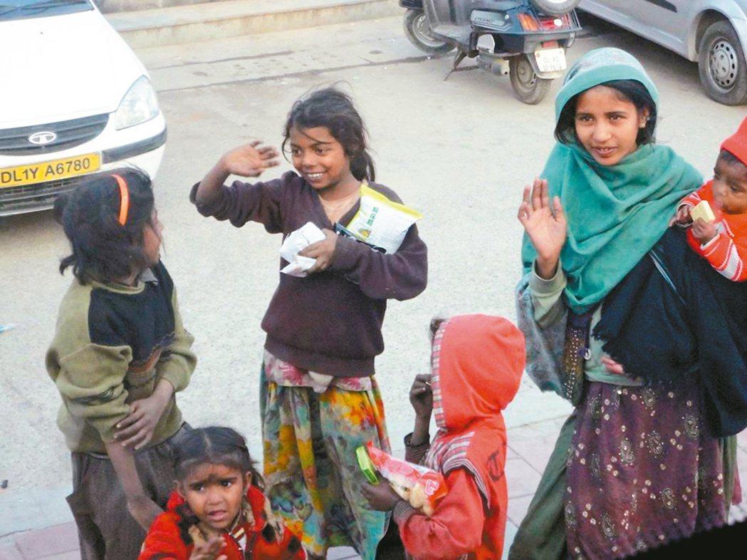 在印度旅行接近尾聲時,車上的旅伴將手中的零食包送給車外的孩子們。 圖/巢佳苓提供