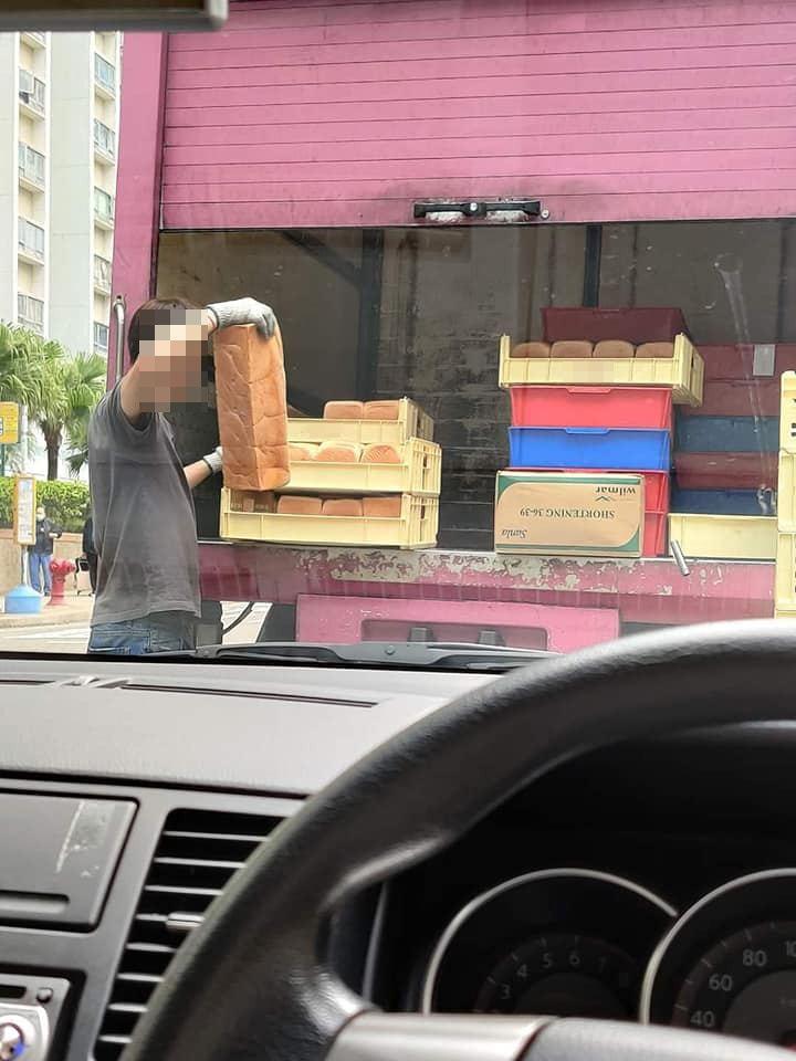 男送貨員補貨時,兩手戴上灰手套,整理一盤盤麵包。圖翻攝自臉書