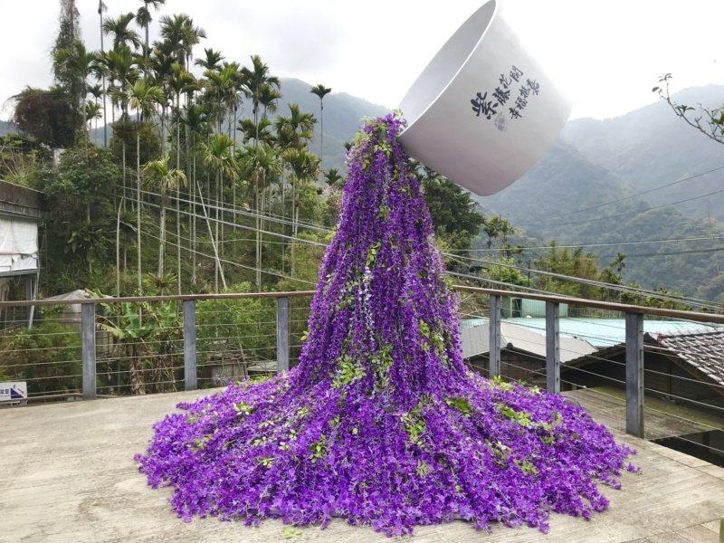 源興宮前廣場推出以紫藤花設計的「捻花舞茶」裝置藝術,大片紫色花瀑從巨大杯流瀉而出...