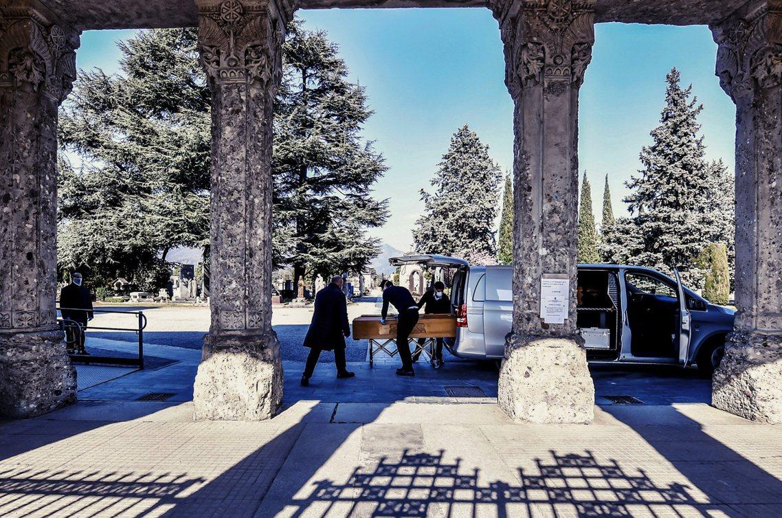 貝加莫省的殯葬人員將病逝患者的棺木運往墓園。 圖/美聯社