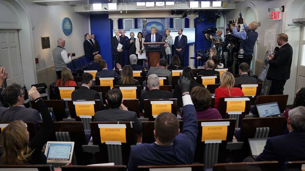 川普在白宮舉行記者會時,為顧慮疫情,記者席已刻意拉開距離。 (美聯社)