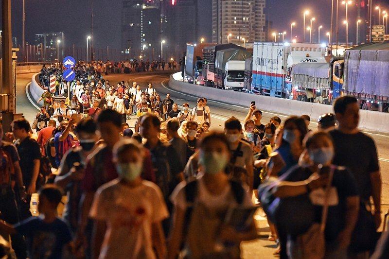 馬來西亞宣布3月18日起實施「行動管理限制」措施。圖為封關前出境至新加坡的馬來西亞人,攝於3月17日。  圖/歐新社