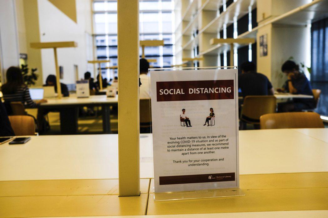 圖為新加坡國家圖書館的安全社交距離告示,攝於3月16日。 圖/美聯社