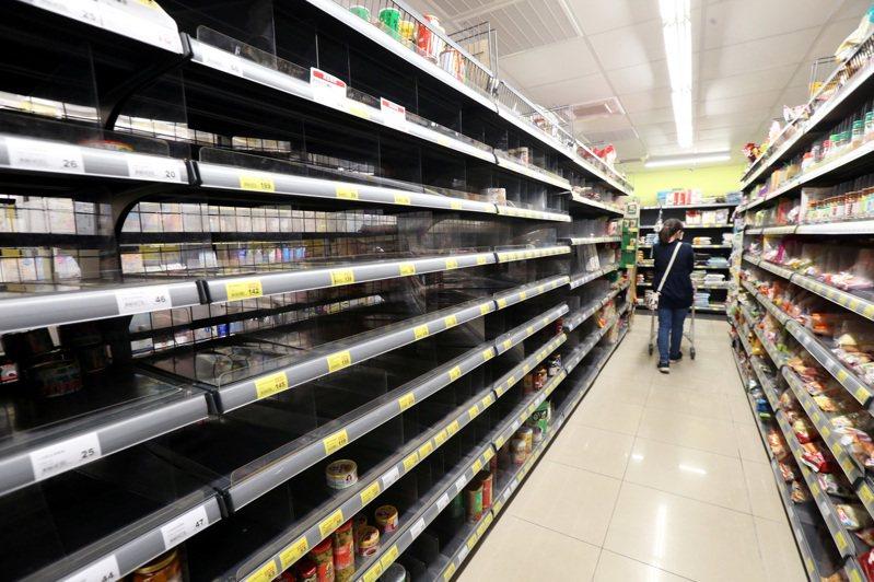 新冠肺炎疫情持續升溫,各賣場及超市的民生物資現搶購潮,今天上午賣場的罐頭商品貨架已空蕩蕩。記者侯永全/攝影