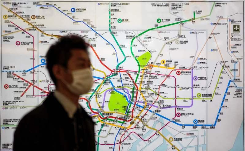 圖為戴口罩的男子在東京車站走過電車地圖。法新社