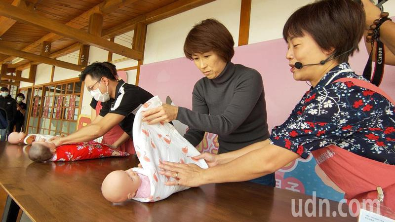 台東縣長饒慶鈴(右二)在月嫂指導下,學習幫新生兒包包巾。記者羅紹平/攝影