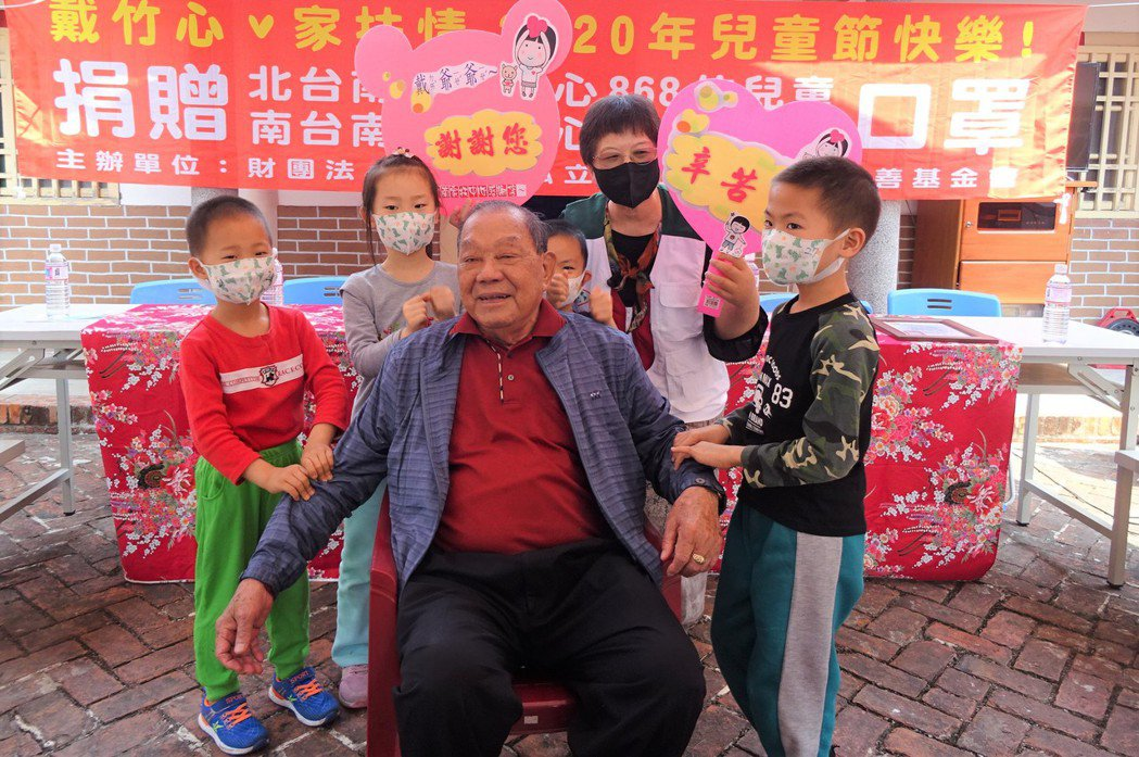 康那香董事長戴榮吉(中)贈送口罩給家扶中心,小朋友為「戴爺爺」捶背回報。圖/北家...