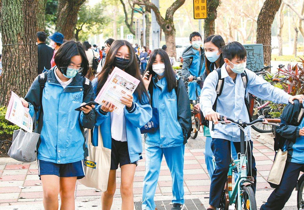 北部某高中因學生染疫而停課,校園防疫成焦點。圖為學生戴口罩進出校園,量測體溫(示...