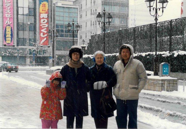 魏崢(右1)與母親(右2)長相神似,多年前於大雪紛飛的日本合影,母親樂觀開朗,目...
