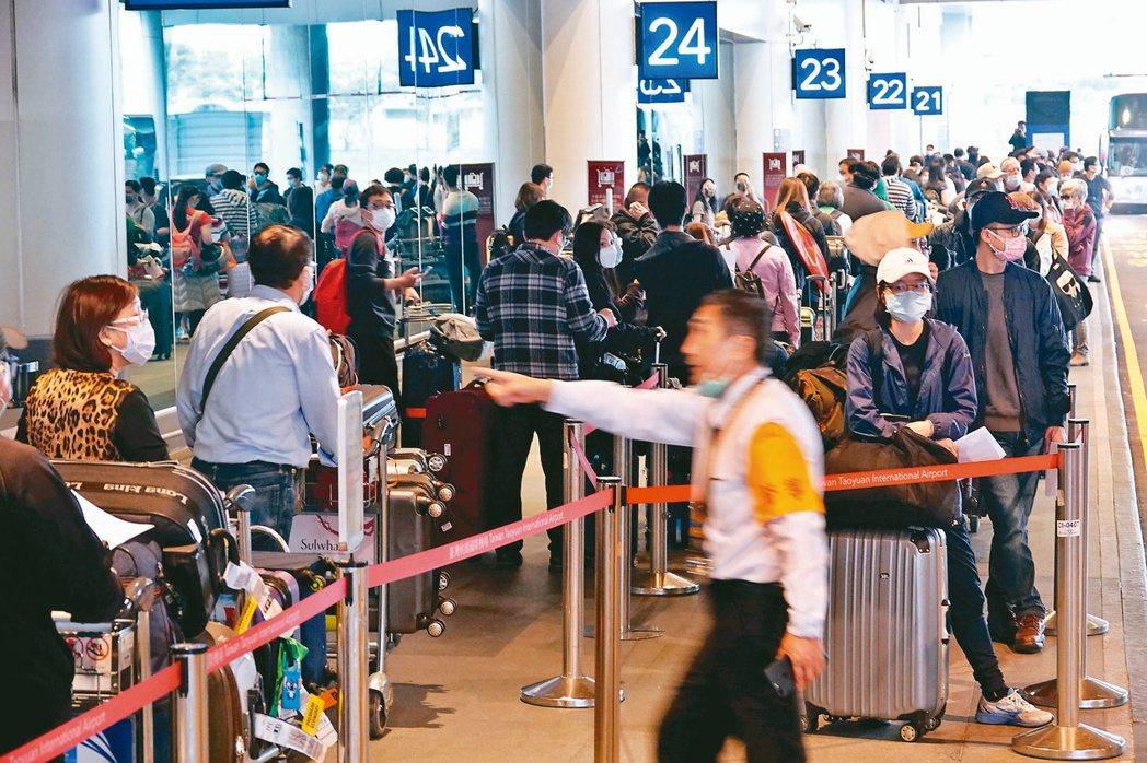 在桃園機場等候防疫計程車的旅客大排長龍,為防止境外移入,入境後均要居家檢疫14天...