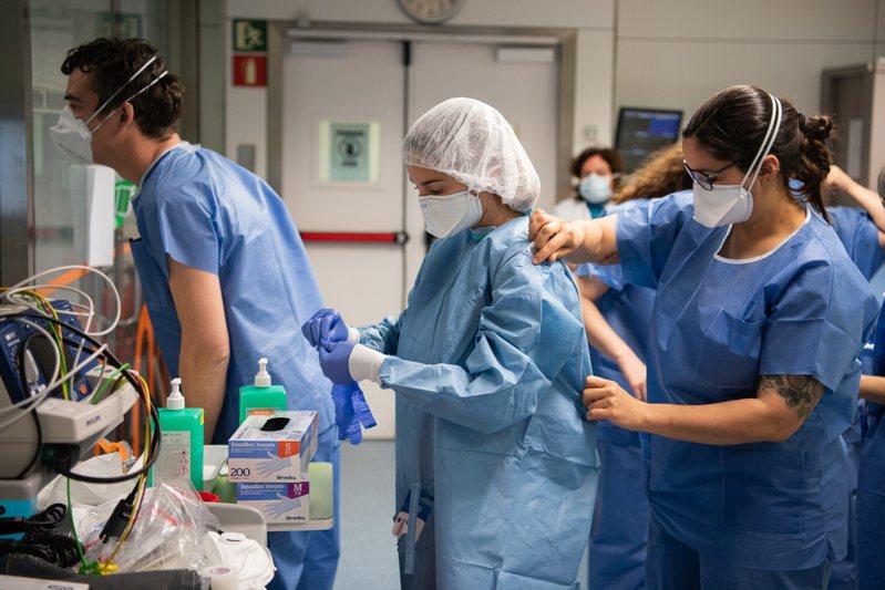 病患爆量,裝備不足,西班牙和義大利醫護人員因應新冠肺炎危機捉襟見肘。圖為西班牙巴塞隆納一間醫院的醫護人員正在穿防護衣。新華社
