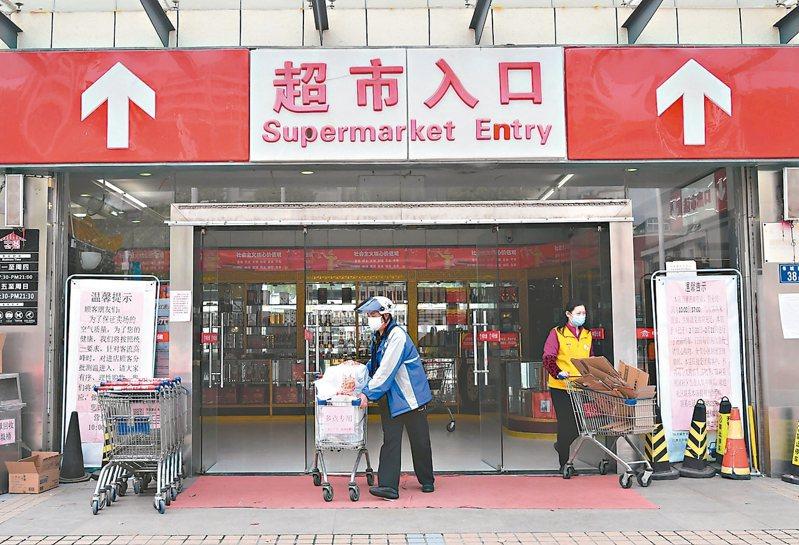 武漢超市恢復正常營業,進店採購前除出示電子健康碼外,還要測體溫。 (中新社)