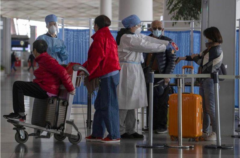 北京機場人員為抵京人士檢測體溫。(美聯社)