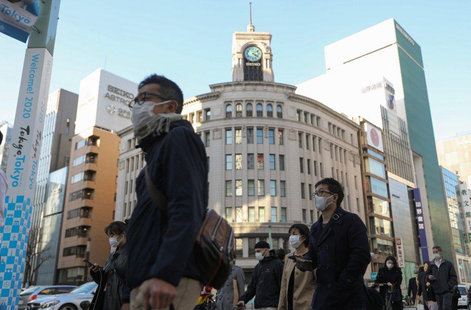 日本境內25日新增96起2019新冠病毒確診感染例,創下單日新高紀錄。圖為日本東京銀座,行人戴口罩出行。 新華社