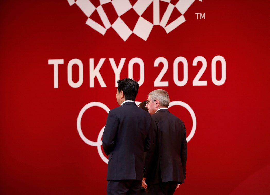 日本首相安倍(左)24日與國際奧會主席巴赫(右)通電話,建議奧運延後一年舉行。圖...