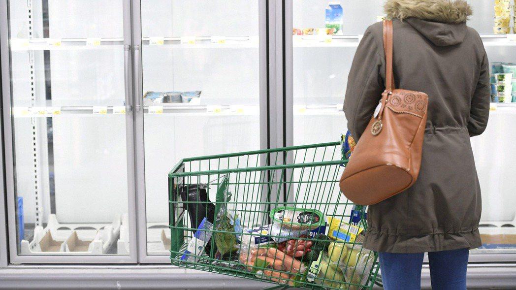 芬蘭超市一位民眾望著被搶購一空的食品架。 路透社