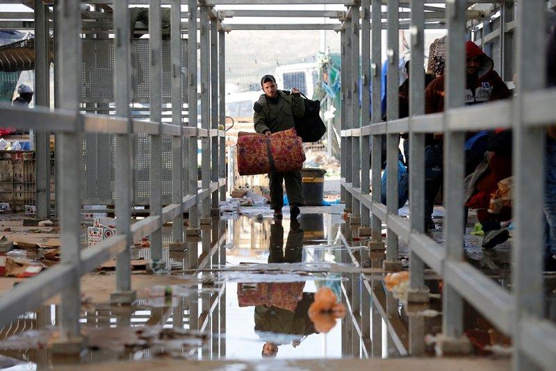 圖為巴勒斯坦人跨越位於希伯侖附近的以色列海關去上班,攝於3月19日。 圖/路透社