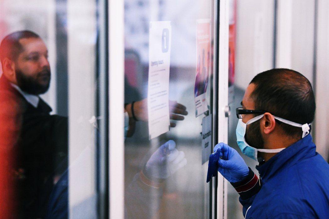 圖為封鎖之後,英國醫護人員在超市門口出示證件。 圖/法新社