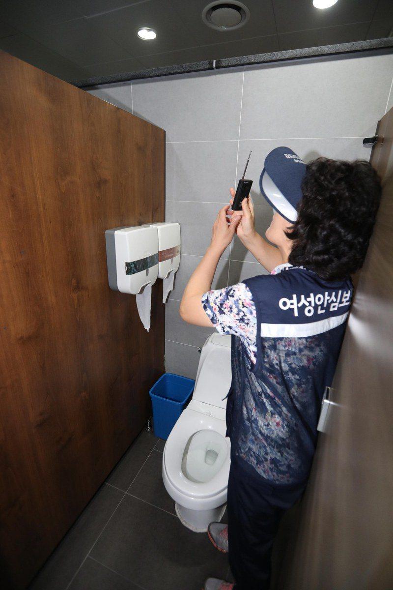 南韓偷拍犯罪猖獗,圖為一名檢測人員在公廁檢查是否有安裝偷拍相機。(歐新社)