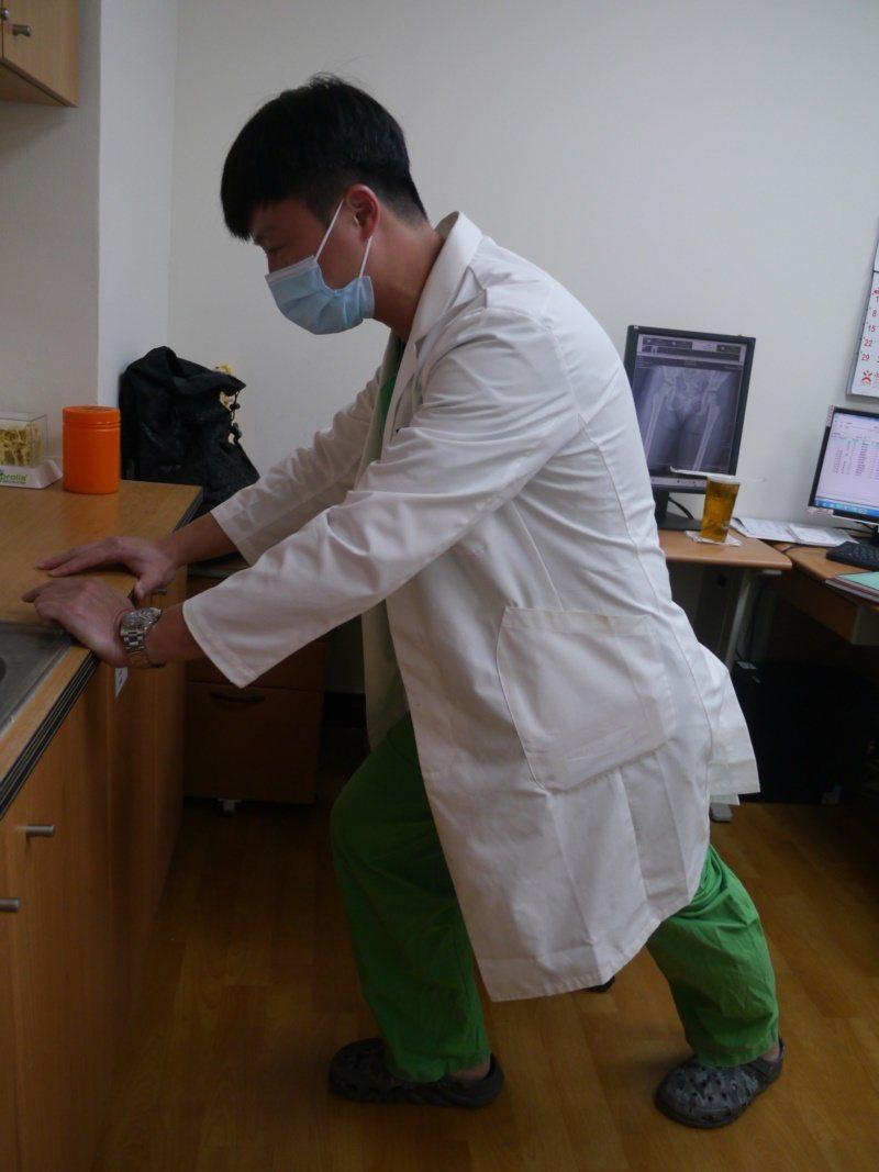 骨科醫師林書樊示範登山前暖身運動,可以扶著牆壁這樣拉筋。 圖/徐白櫻 攝影