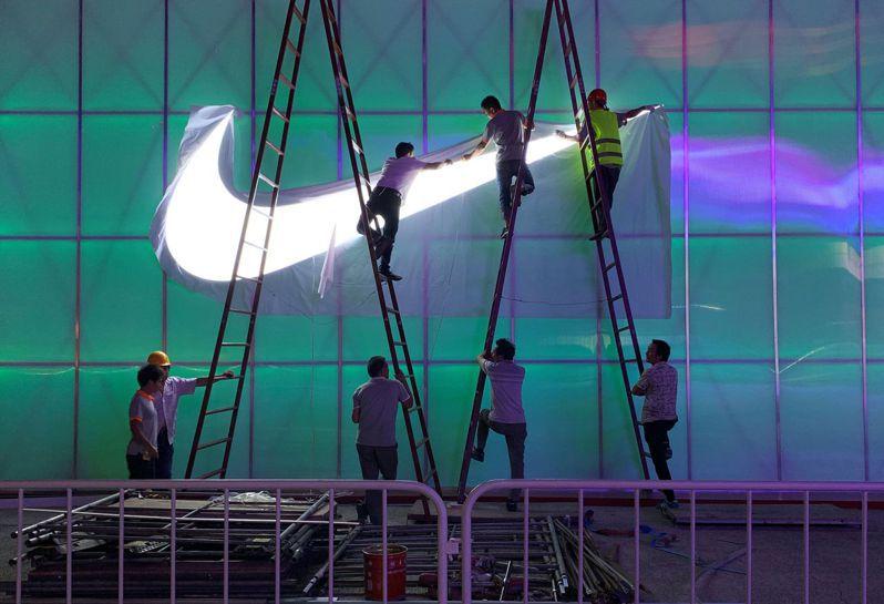工作人員去年在中國大陸北京五棵松體育館外,安裝Nike商標的檔案照。  路透