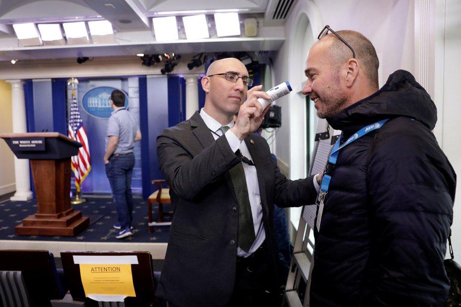 23日的白宫記者會前,白宮幕僚為法新社記者測體溫。路透