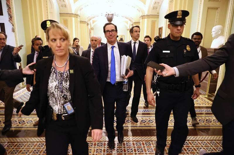 在國會兩黨有望就兩兆美元紓困案達協議後,美國財長米努勤(中)22日晚間笑著離開參院少數黨領袖舒默的辦公室。法新社